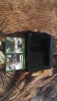 Black xbox one console with game cases