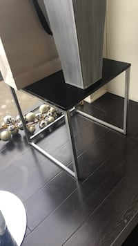 square black marble-top table with stainless steel frame
