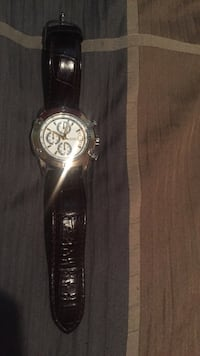 Round silver and white chronograph watch with brown leather strap. Guess collection