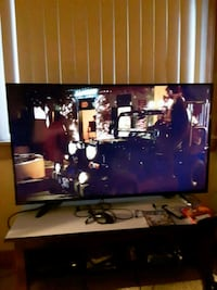 black flat screen TV; black wooden TV stand