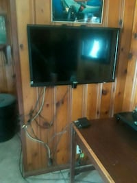 flat screen television with brown wooden TV stand Beaumont, 77703