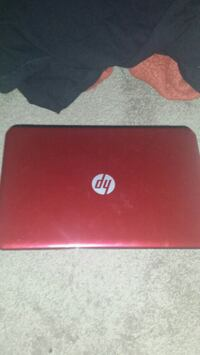 red HP laptop with AC adapter