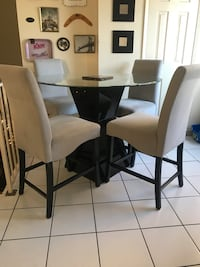 Circle glass top table with four chairs