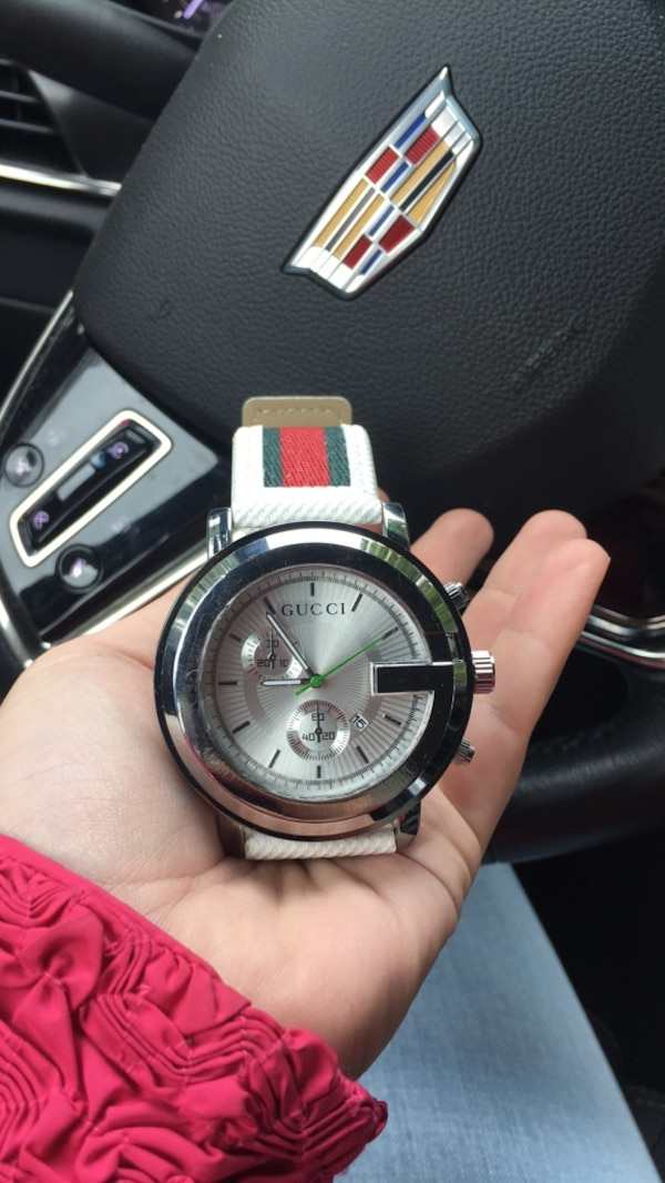 round silver-colored chronograph watch with white strap