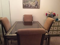 Dining tale and 4 upholstered chairs.  Glass top brass frame 40x52 extends to 104 when opened New York, 10075