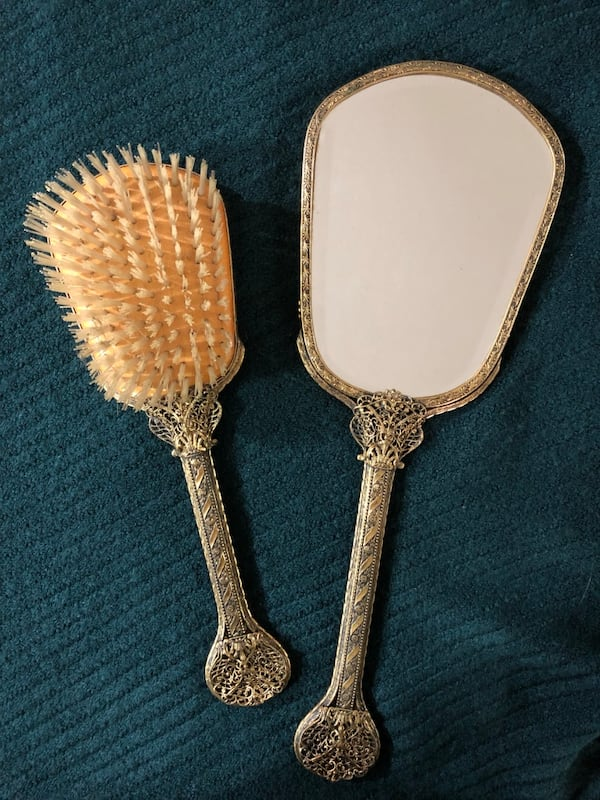 Vintage mirror and brush set with intricate detail on the handles 1a4337ba-7eef-40da-a400-40a45795e041