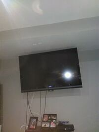 flat screen TV and brown wooden TV stand 554 km