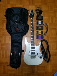 white Ibanez electric guitar with black soft case, and five assorted-color distortions