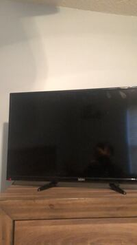 black flat screen TV with remote Sterling Heights, 48311