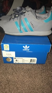 pair of gray Adidas Samoa sneakers with blue box