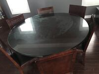 Dining Table made of solid wood and glass top. It includes 6 chairs with top grain leather Cover. Glass top has an additional glass smaller glass top that rotates with a lazy susan (lazy susan not available). In very good condition Aurora, L4G 0G1