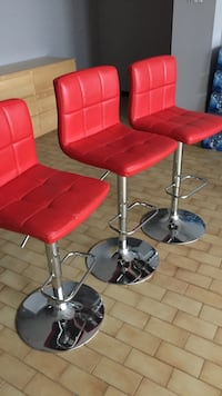 Three red leather padded bar stools