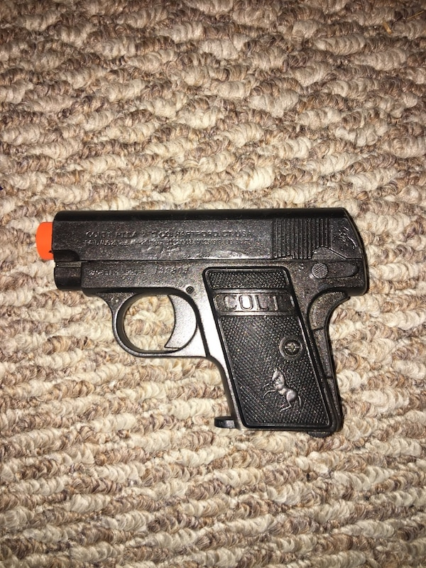 Black and orange airsoft handgun with bag of ammo