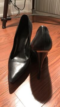 pair of black leather pointed-toe heeled shoes