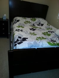 Dark wood bed with white, green, gray, and black floral print bedspread