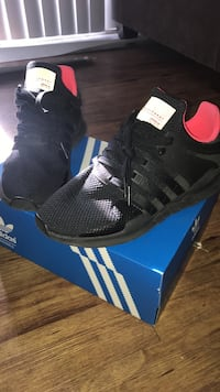 Pair of black-and-pink adidas running shoes with box