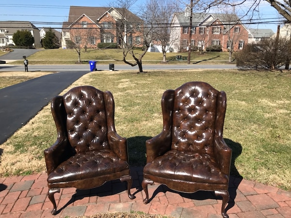 Two Brown leather tufted wing chairs