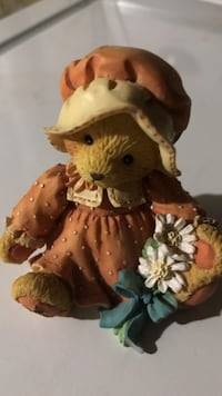 orange dressed bear ceramic figurine