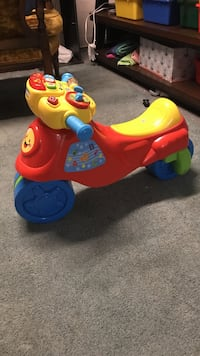 toddler's red, yellow, and blue motorcycle ride-on toy