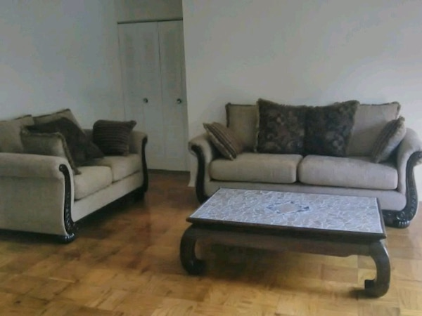 Tan and brown sofa and love seat and coffee table