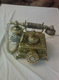 vintage gold- and silver-colored rotary telephone