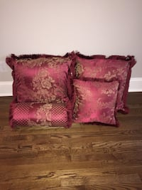 Four rose and gold colored  throw pillows
