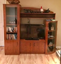 black flat screen TV and brown wooden entertainment center