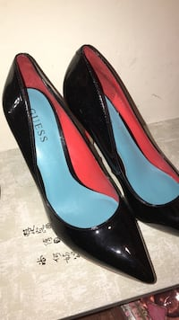 pair of women's black Guess leather pointed-toe pumps