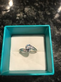silver-colored ring with clear gemstones and box