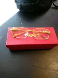 gold-colored framed eyeglasses with box