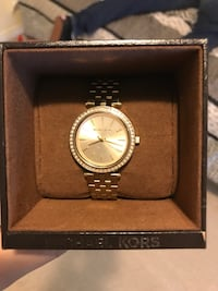 Round gold-colored analog watch with link bracelet with box