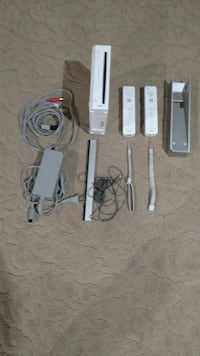 white Wii, two controllers, and gray AC adapter