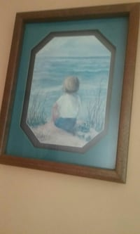 child seating in front of ocean painting
