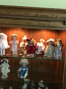 assorted doll lot in cabinet