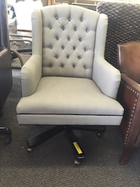 gray tufted rolling armchair