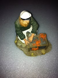 fishing man sitting in front of crab figurine TOMSRIVER