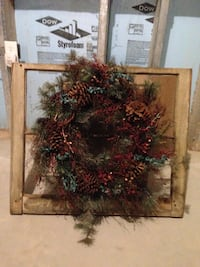 Red and green christmas wreath with old 6 pane , full size window frame behind