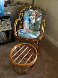 brown rattan armchair with ottoman and blue and pink floral cushion