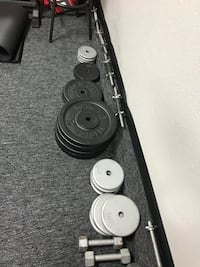 Assorted gym weights and two grey dumbbells