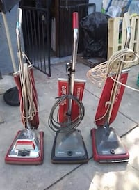 two red and black upright vacuum cleaners