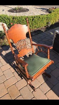 Antique wood glider with green fabric padded seat