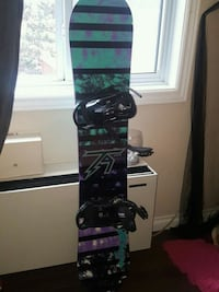 green and black striped snowboard with bindings