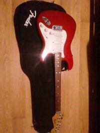 red and white Fender stratocaster electric guitar with gig bag