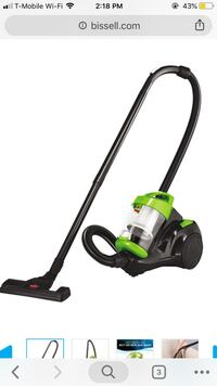 green and black canister vacuum cleaner 12 km