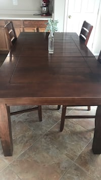 rectangular brown wooden dining table with chairs