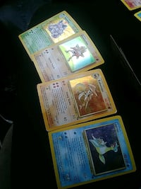 four assorted Pokemon trading cards