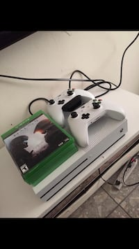 Xbox One console with two controllers and game cases