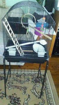 black  pet cage on stand with nesting box