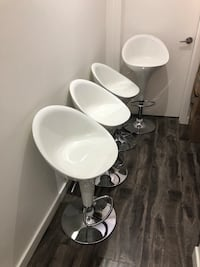 Four white bar stools