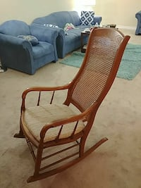 beige padded rocking chair with brown wooden frame